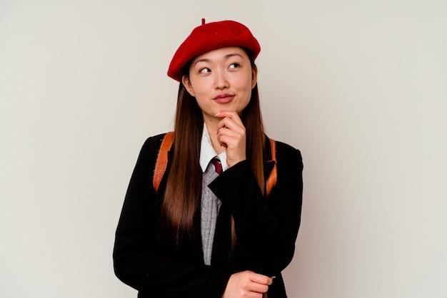 Giovane donna cinese che indossa un'uniforme scolastica isolata sul muro bianco che guarda lateralmente con espressione dubbiosa e scettica