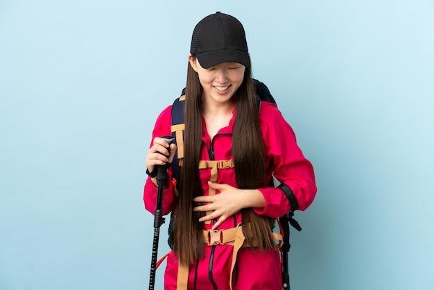 Giovane donna cinese con i pali di trekking e dello zaino sopra la parete blu isolata che sorride molto