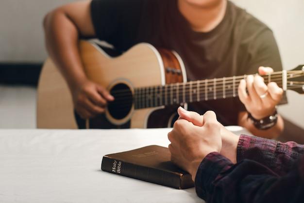 Giovane cristiano che prega con le parole e canta lodi a dio leggendo le scritture e condividendo il vangelo con lo spazio della copia
