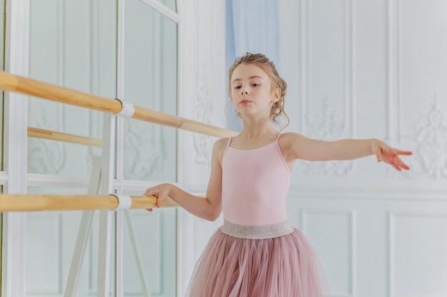 Ragazza giovane ballerina classica in classe di danza in gonna tutu rosa vicino al grande specchio