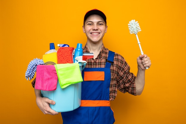 Giovane addetto alle pulizie che indossa l'uniforme e il berretto che tiene il secchio degli strumenti per la pulizia e la spazzola isolati sulla parete arancione