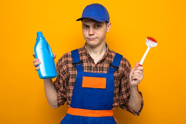 Giovane addetto alle pulizie che indossa l'uniforme e il berretto che tiene il detergente con la spazzola isolata sulla parete arancione
