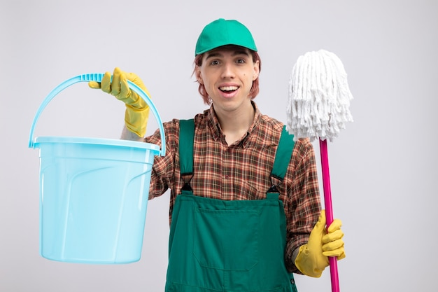 Giovane uomo delle pulizie in tuta da camicia a quadri e berretto che tiene secchio e scopa felice ed eccitato in piedi sul muro bianco