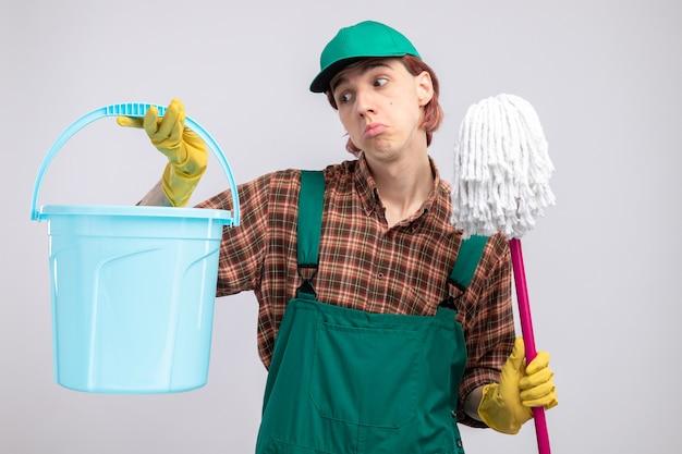 Giovane uomo delle pulizie in tuta da camicia a quadri e berretto che tiene secchio e mocio guardando il secchio confuso in piedi sul muro bianco