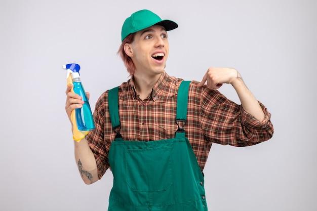 Giovane uomo delle pulizie in tuta a quadri e berretto che tiene in mano uno straccio e uno spray per la pulizia che guarda da parte felice ed eccitato
