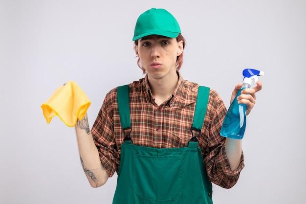 Giovane uomo delle pulizie in tuta da camicia a quadri e berretto che tiene in mano uno straccio e uno spray per la pulizia che guarda con una faccia seria