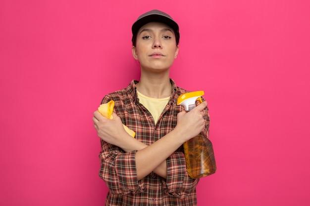 Giovane donna delle pulizie in abiti casual e berretto che tiene straccio e spray detergente con espressione seria e sicura che incrocia le mani in piedi sul rosa