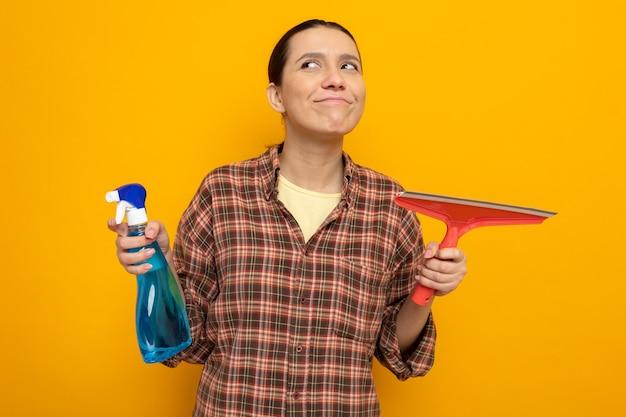 Giovane donna delle pulizie in abiti casual che tiene in mano uno spray detergente e uno straccio che guarda da parte sorridendo felice e positivo