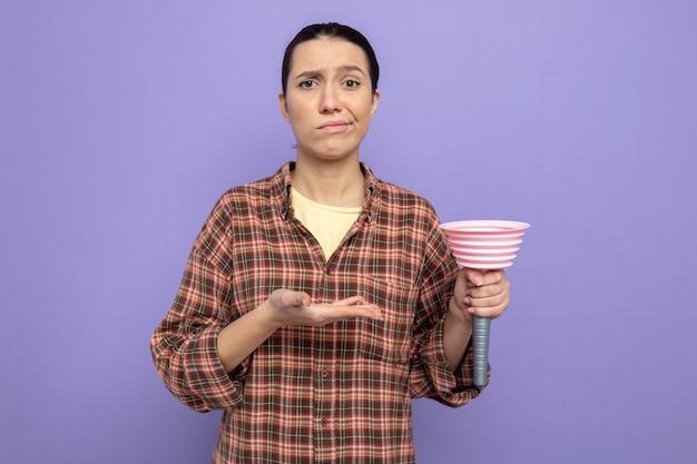 Giovane donna delle pulizie in abiti casual che tiene lo stantuffo che lo presenta con il braccio della mano che sembra dispiaciuto in piedi sul muro viola