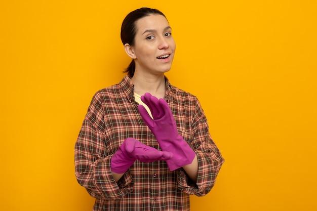 Giovane donna delle pulizie in abiti casual con guanti di gomma che applaudono felici e fiduciosi in piedi sull'arancia