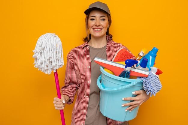 Giovane donna delle pulizie in camicia a quadri e berretto che tiene il secchio con strumenti per la pulizia e mocio dall'aspetto felice e positivo sorridente pronto per la pulizia