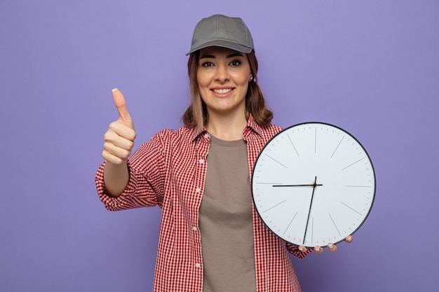 Giovane donna delle pulizie in camicia a quadri e berretto che tiene l'orologio che sorride allegramente mostrando i pollici in su