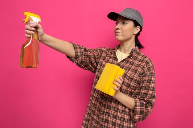 Giovane donna delle pulizie in camicia a quadri e berretto in guanti di gomma che tiene in mano una spugna e uno spray per la pulizia che sembra sicura pronta per la pulizia