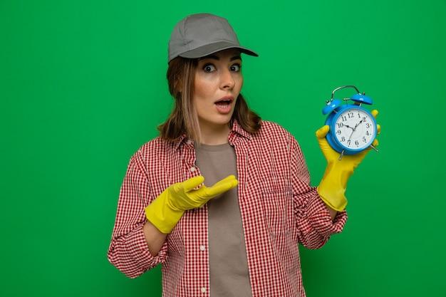 Giovane donna delle pulizie in camicia a quadri e berretto che indossa guanti di gomma tenendo la sveglia presentandola con il braccio guardando la telecamera confusa in piedi su sfondo verde