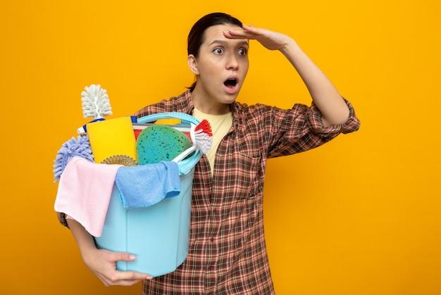 Giovane donna delle pulizie in camicia a quadri che tiene in mano un secchio con strumenti per la pulizia che guarda lontano con la mano sulla testa stupita e sorpresa in piedi sull'arancia