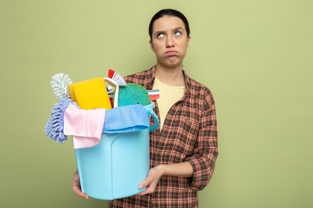 Giovane donna delle pulizie in camicia a quadri che tiene il secchio con strumenti per la pulizia che guarda le guance stanche e lavorate che soffiano in piedi sul verde