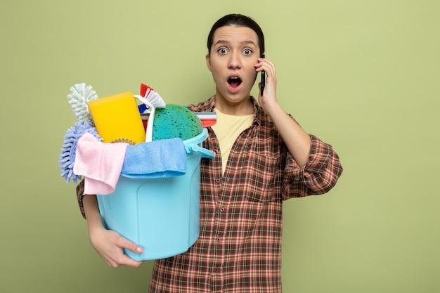 Giovane donna delle pulizie in camicia a quadri che tiene in mano un secchio con strumenti per la pulizia sorpresa mentre parla al telefono cellulare in piedi sul verde