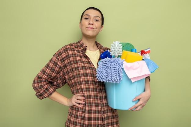 Giovane donna delle pulizie in camicia a quadri che tiene secchio con strumenti per la pulizia con espressione sicura sorridente in piedi sul verde