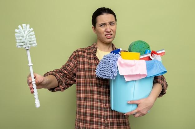 Giovane donna delle pulizie in camicia a quadri che tiene in mano una spazzola per la pulizia e un secchio con strumenti per la pulizia che sembra confusa con un'espressione disgustata in piedi sul verde
