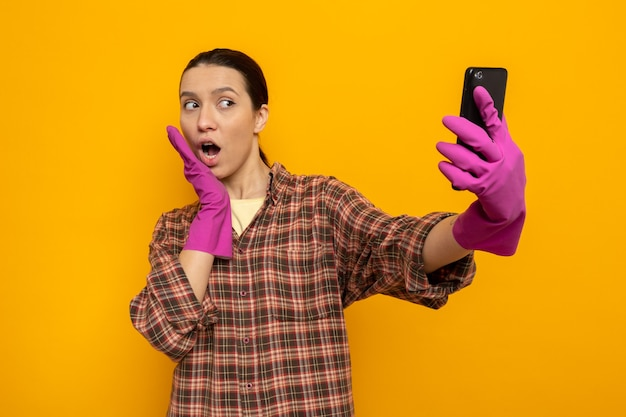 Giovane donna delle pulizie in camicia a quadri in guanti di gomma che tiene smartphone facendo selfie felice e sorpreso in piedi sull'arancia