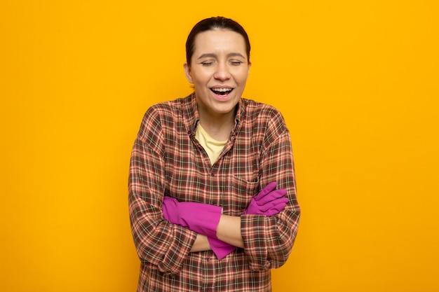 Giovane donna delle pulizie in camicia a quadri in guanti di gomma che ride con le braccia incrociate in piedi sul muro arancione