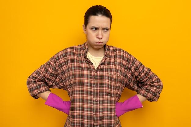 Giovane donna delle pulizie in camicia a quadri in guanti di gomma che guarda da parte dispiaciuta che soffia le guance con le braccia all'anca