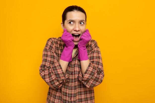 Giovane donna delle pulizie in camicia a quadri in guanti di gomma che guarda da parte felice ed eccitata tenendosi per mano insieme