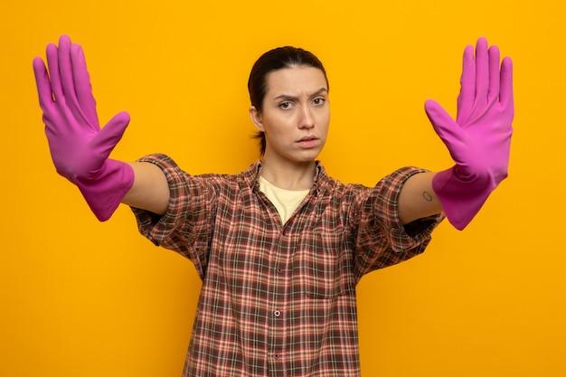Giovane donna delle pulizie in camicia a quadri in guanti di gomma che guarda davanti con una faccia seria che fa un gesto di arresto con le mani in piedi sul muro arancione