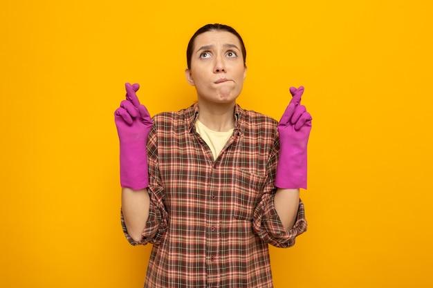 Giovane donna delle pulizie in camicia a quadri in guanti di gomma che esprime il desiderio desiderabile incrociando le dita con l'espressione di speranza in piedi sul muro arancione