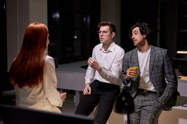 Giovani colleghi in abiti formali conversano, fanno una pausa a tarda notte nella sala riunioni, sorridono, discutono, condividono idee, spiegano piani. lavoro di squadra, concetto di impiegati