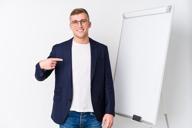Giovane uomo di coaching che mostra una persona del bordo bianco che indica a mano uno spazio della copia della camicia, orgoglioso e fiducioso