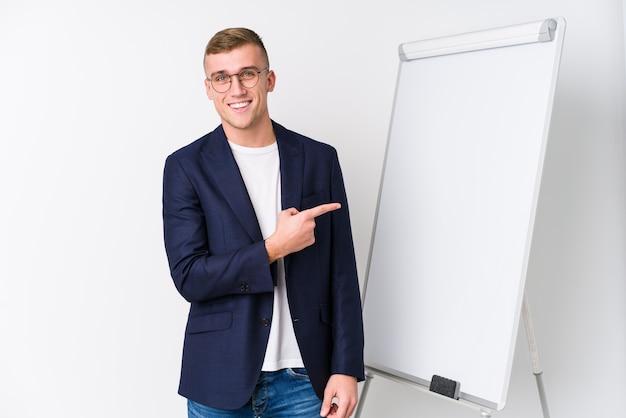 Giovane uomo di coaching che mostra un bordo bianco che sorride e che indica da parte, mostrando qualcosa nello spazio vuoto.