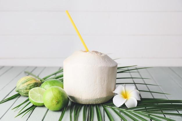 Giovane noce di cocco con paglia e limette sul tavolo Foto Premium