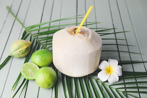 Giovane noce di cocco con paglia e limette sul tavolo