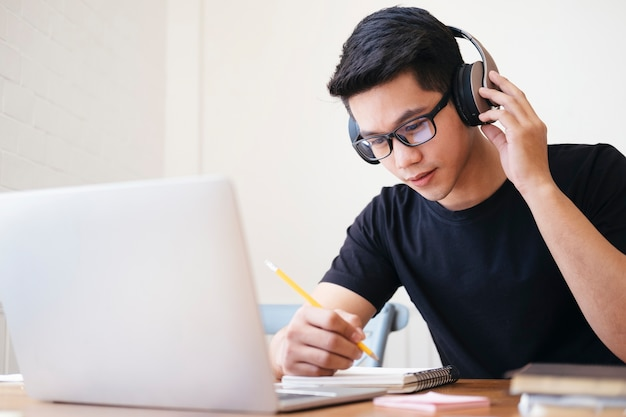 Giovane studente di collage utilizzando computer e dispositivo mobile studiando online. istruzione e apprendimento online.