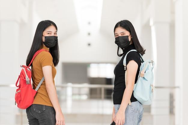 Giovane studente di college che indossa una maschera di panno nero, torna a scuola,