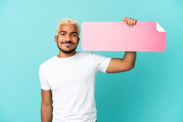 Giovane bell'uomo colombiano isolato su sfondo blu con in mano un cartello vuoto