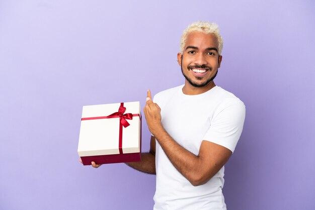 Giovane uomo colombiano che tiene un regalo isolato su sfondo viola che punta indietro