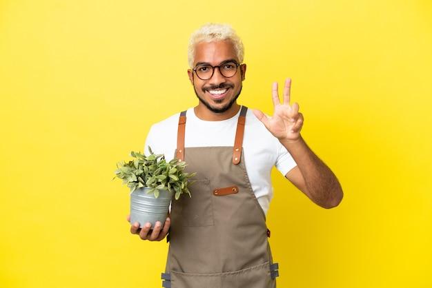 Giovane uomo colombiano che tiene una pianta isolata su sfondo giallo felice e conta tre con le dita