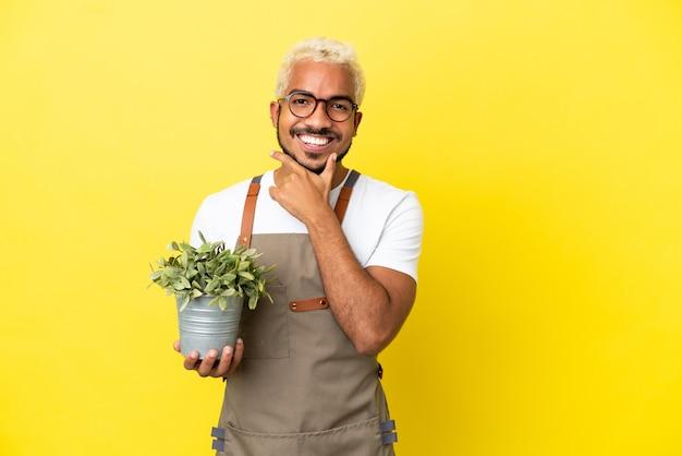 Giovane uomo colombiano in possesso di una pianta isolata su sfondo giallo felice e sorridente