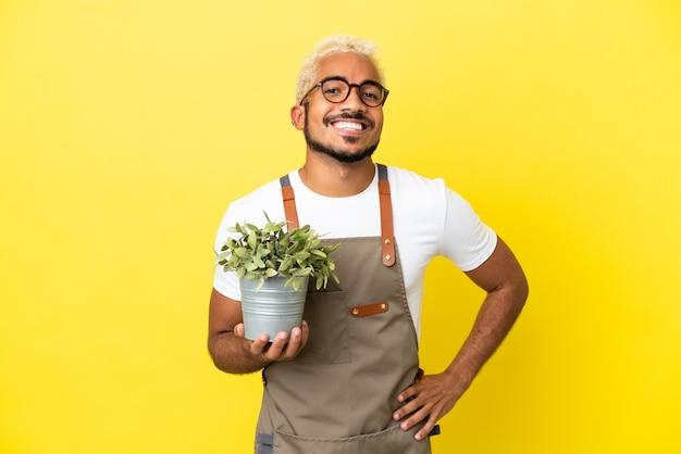 Giovane uomo colombiano in possesso di una pianta isolata su sfondo giallo in posa con le braccia all'anca e sorridente