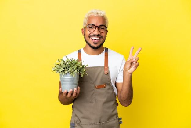 Giovane uomo colombiano in possesso di una pianta isolata su sfondo giallo sorridente e mostrando segno di vittoria