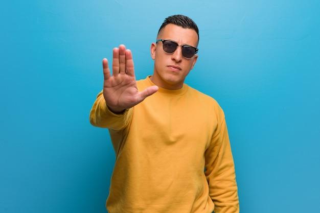 Giovane uomo colombiano che mette la mano davanti