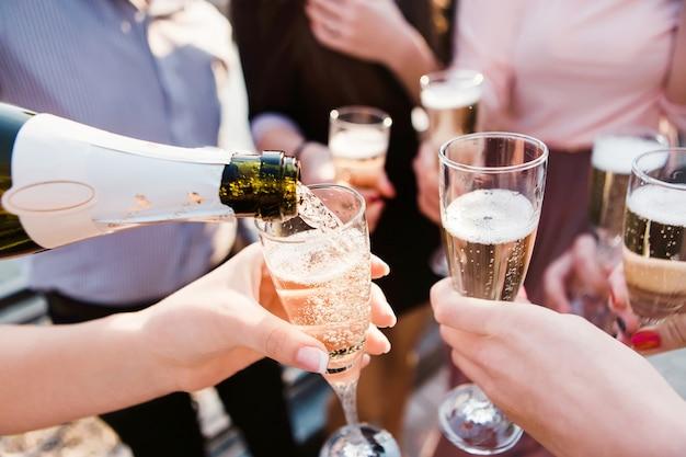 Giovane azienda che versa champagne nei calici. giovani ragazzi bevono champagne al tramonto. spumante in calici di vetro. spruzzi di champagne