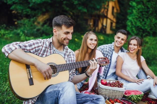 Una giovane compagnia di studenti trascorre i fine settimana nel parco e un ragazzo bruna suona la chitarra