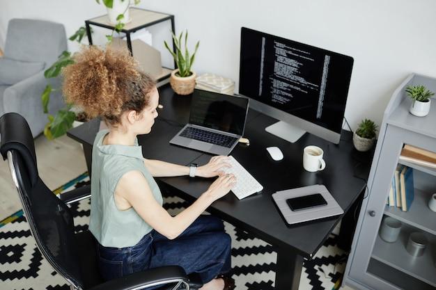 Giovane programmatrice di computer che lavora con il software sul posto di lavoro in ufficio