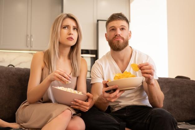 Giovani coppie europee concentrate si siedono sul divano e guardano la tv o un film. ragazzo e ragazza che mangiano patatine e popcorn. tempo libero e riposo a casa. concetto di godersi il tempo insieme. interno del monolocale