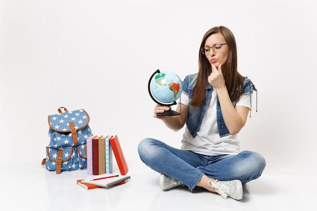 Giovane studentessa concentrata con gli occhiali che guarda il globo del mondo, tenendo la mano sul mento seduta vicino allo zaino, libri di scuola isolati sul muro bianco