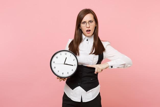 Giovane donna d'affari interessata in tuta e occhiali che punta il dito indice sulla sveglia isolata su sfondo rosa pastello. signora capo. concetto di ricchezza di carriera di successo. copia spazio per la pubblicità.