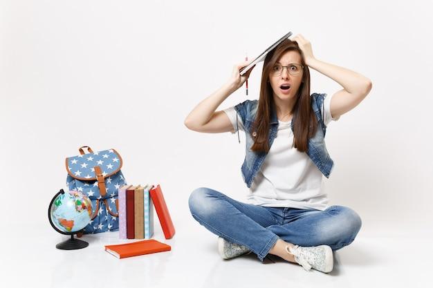 La giovane studentessa preoccupata perplessa in vetri tiene la matita, il taccuino aggrappato alla testa si siede vicino allo zaino del globo, libri di scuola isolati sulla parete bianca
